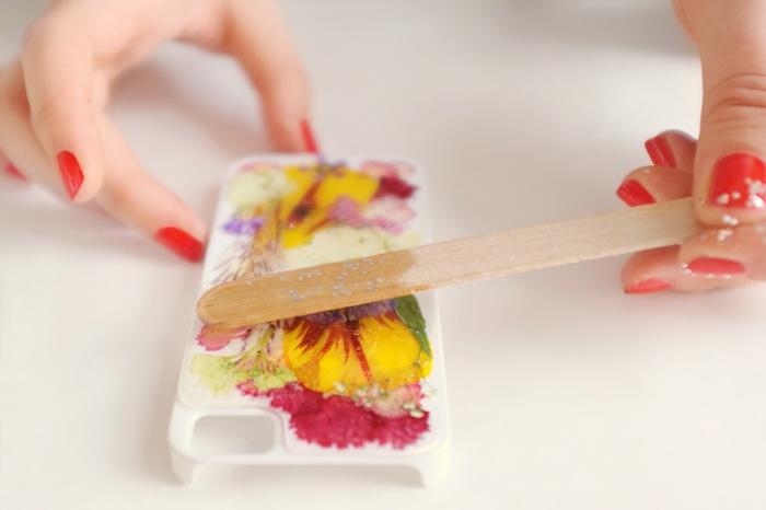 Harz auf weiße Hülle mit gepressten Blumen mit Holzstab aufteilen, Hand mit rotem Nagellack, Handyhülle selber gestalten