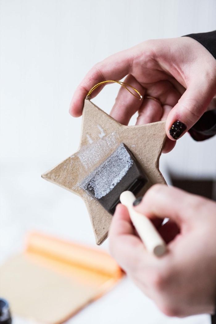 Sterne basteln, tragen Sie Klebstoff über Kartonstern auf, um Blattgold zu kleben