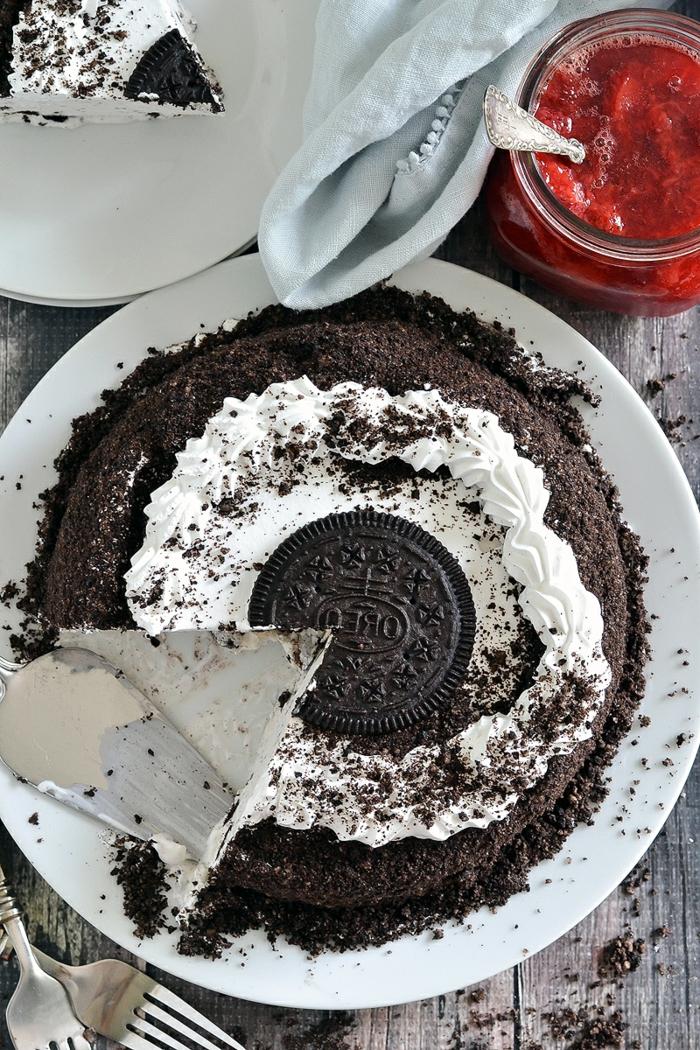 Oreo Kuchen, Milchcreme und viele Oreo Krümmel, ein großer Oreo Keks in der Mitte, rote Grütze zum Servieren