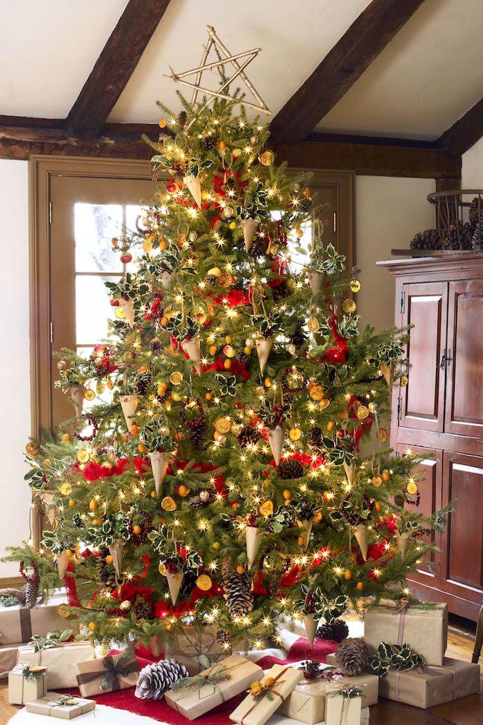 Riesiger echter Weihnachtsbaum mit viel schmuck, viele Weihnachtsgeschenke unter dem Baum