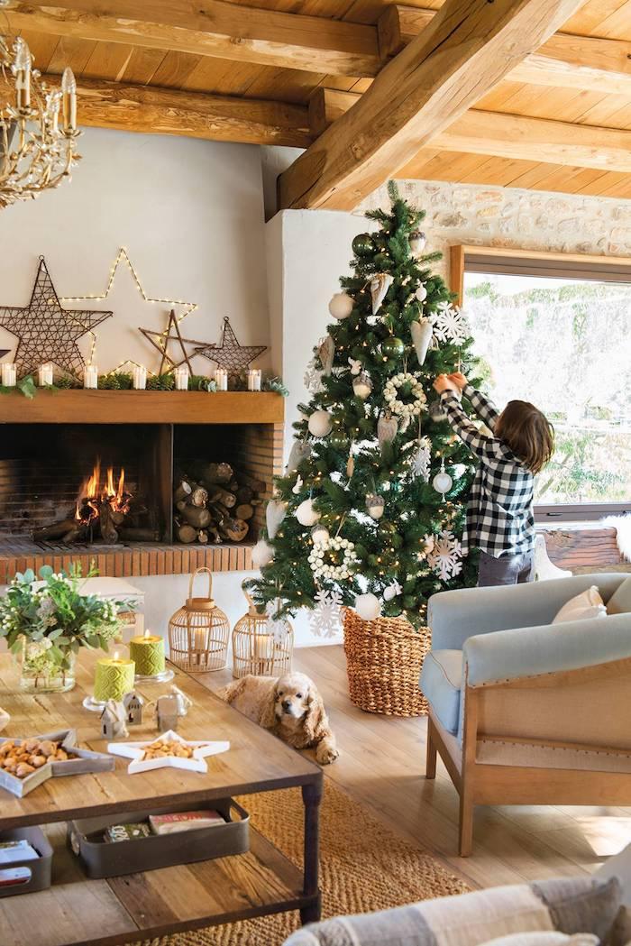 Wohnzimmer im Landhausstil, Christbaum in Rattankorb geschmückt mit weißen Anhängern, Kind schmückt den Tannenbaum