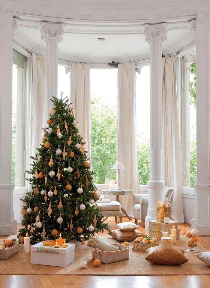 Weihnachtsbaum mit weißen und goldenen Christbaumkugeln, Dekokissen und Geschenkschachteln am Boden