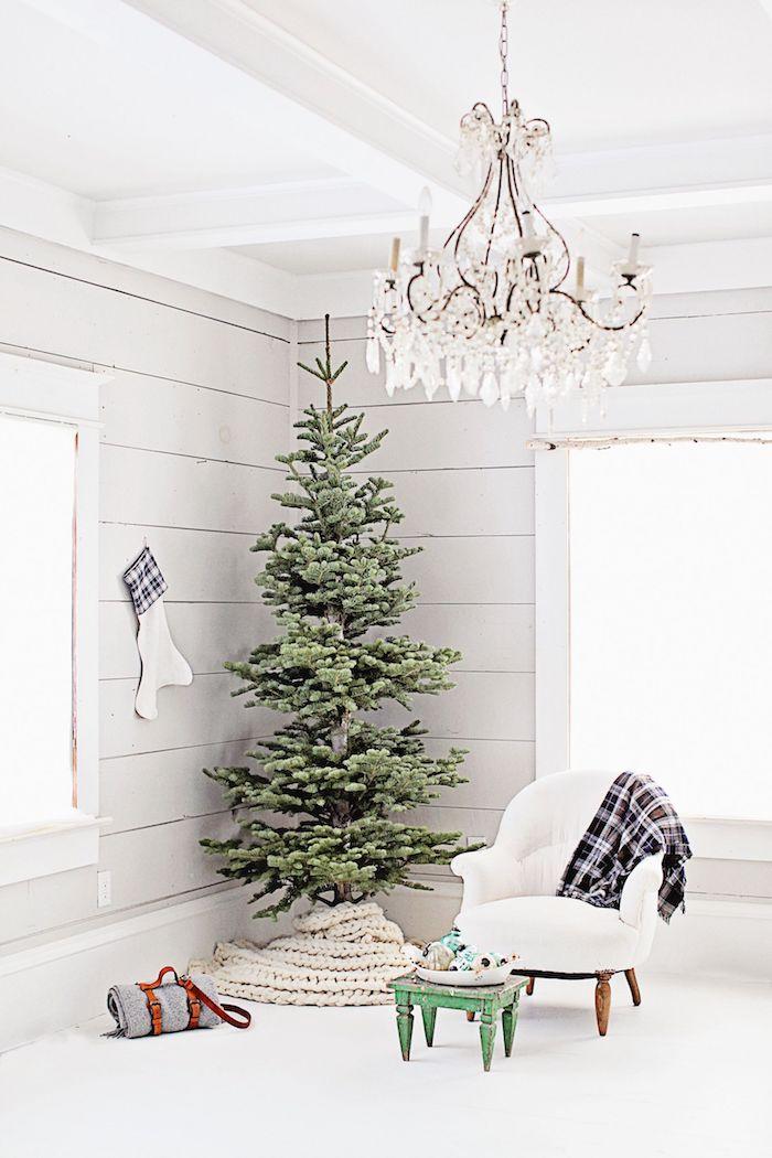 Tannenbaum ohne Schmuck, weiße kuschelige Decke unter dem Baum, weißer Sessel und karierte Decke, verspielter Kronleuchter
