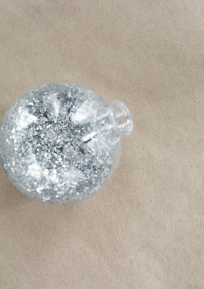 eine durchsichtige Weihnachtskugel mit silbernem Glitter gefüllt, Weihnachtskugel selber machen