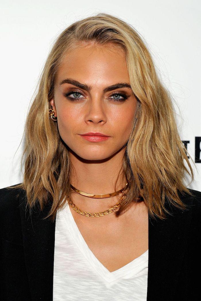Cara Delevingne Haarschnitt, Longbob Frisur, dunkelblonde Haare und gebräunter Teint, Smokey Eyes und roter Lippenstift