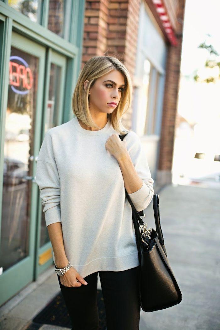 Blonder Bob, glatte schulterlange Haare, weißer Pullover und schwarze Hose, schwarze Ledertasche
