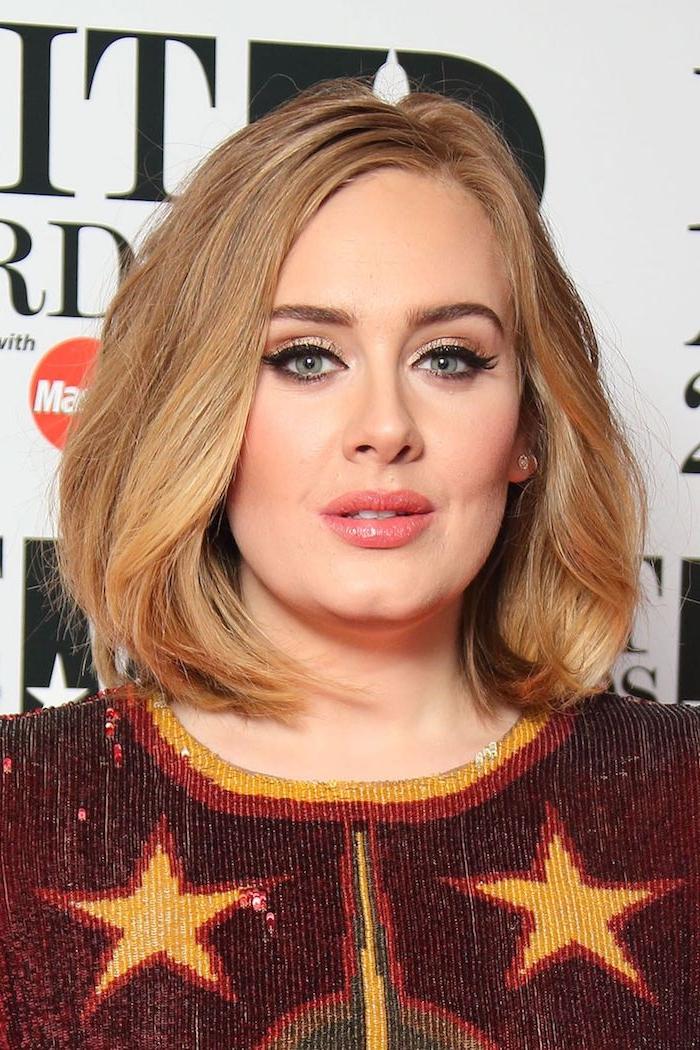 Adele Long Bob Haarschnitt, dunkelblonde Haare mit Seitenscheitel, schwarzer Lidstrich und Lipgloss