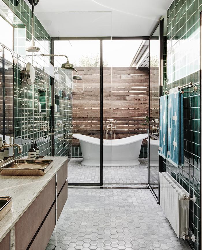 eine kleine weiße freistehende badewanne im badezimmer, eine outdoor dusche