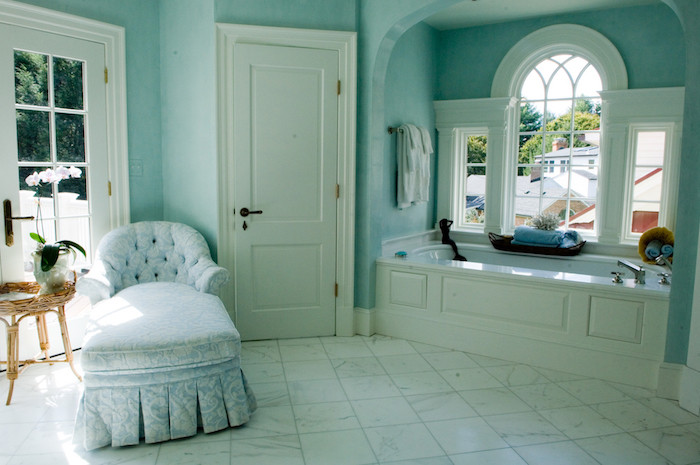 ein tisch mit vasen mit weißen blumen, ein badezimmer mit grünen wänden und fenstern und einer weißen badewanne und weißer tür