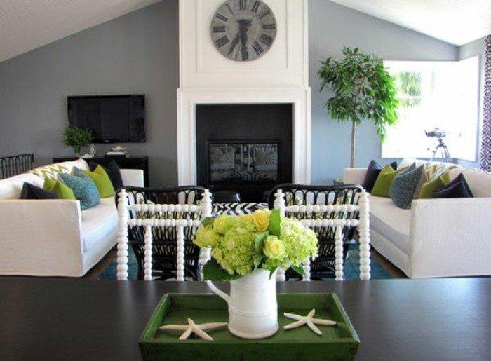 zwei weiße Sofas mit bunten Kissen, eine Wand mit Fernseher und Kamin und großer Wanduhr, Wohnzimmer in Grau Weiß