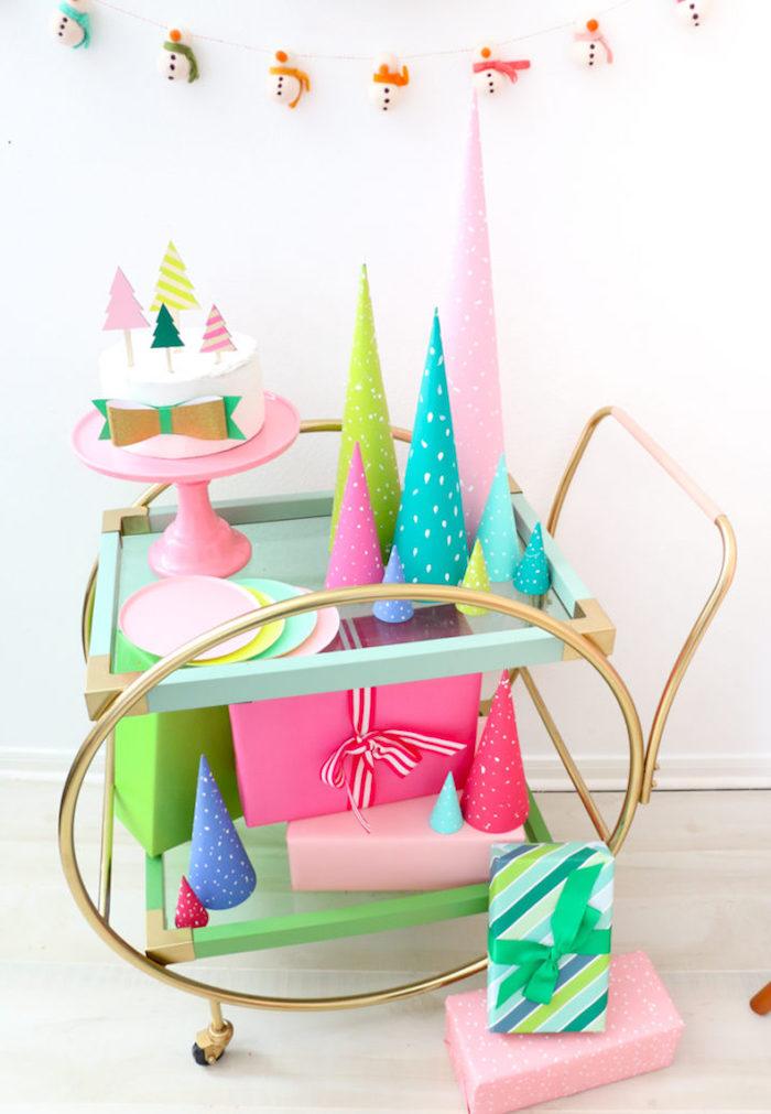 Girlande mit kleinen Schneemännern, bunte Weihnachtsbäume aus Karton, schön verpackte Geschenke, Weihnachtstorte mit Tannenbäumen