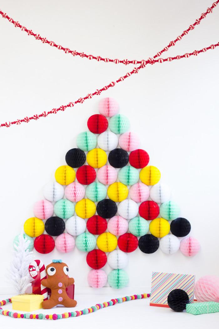 Weihnachtsbaum aus bunten Papierbällen an der Wand, Girlanden aus Papier und kleine Weihnachtsgeschenke