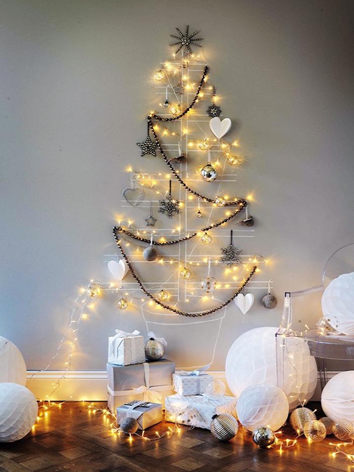 Weihnachtsbaum mit weißer Farbe an die Wand zeichnen, Lichterkette und Anhänger befestigen, Geschenke am Boden