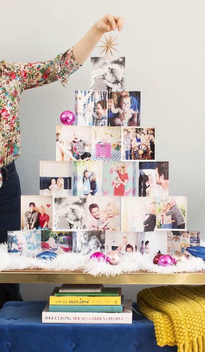 Schöne Alternative zum klassischen Tannenbaum, Weihnachtsbaum aus Bildern, geschmückt mit violetten Weihnachtskugeln und weißen Girlanden