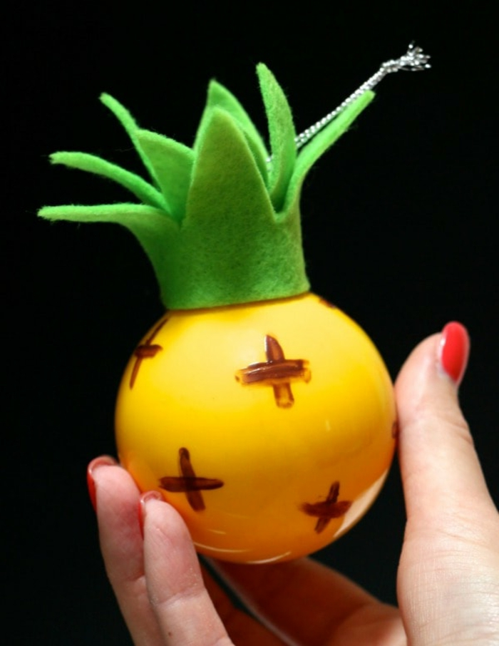 gelber Ananas mit grünen Blättern aus Papier, silberfarbene Schleife, Weihnachtskugeln selber machen