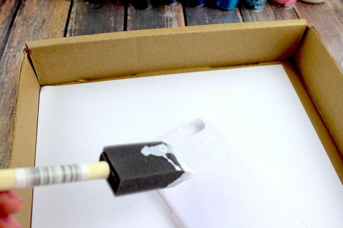 bedecken Sie die weiße Handyhülle mit Klebstoff, Handyhüllen selbst gestalten, tragen Sie mit Pinseln auf