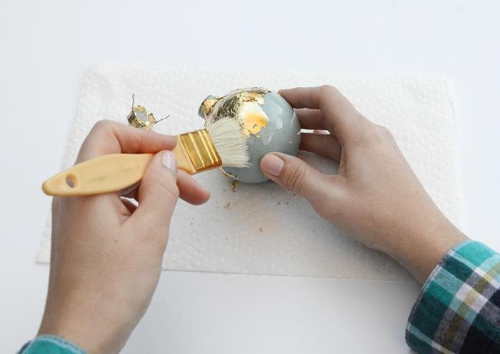 ein graues Bild mit goldener Dekoration beschmücken, mit einer Pinsel bekleben