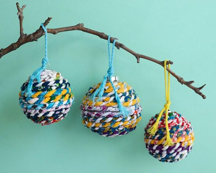 Chistbaumkugeln in vielen Farben, hängen von einem Stock, drei Stücke in verschiedenen Größen