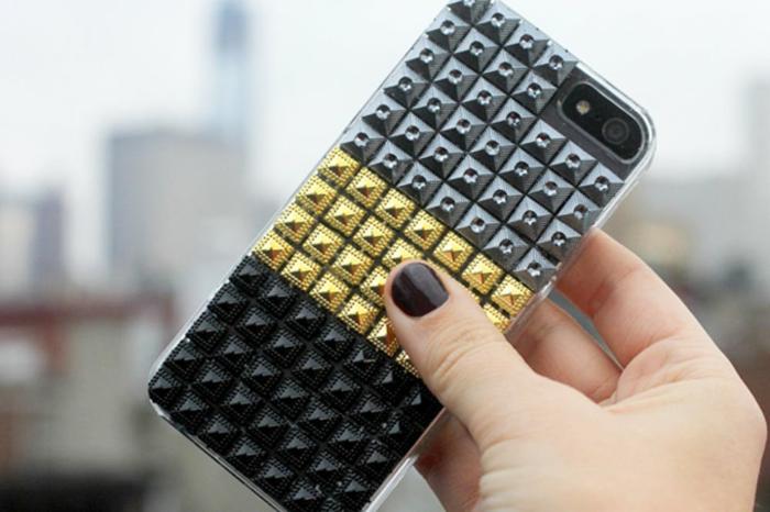 eine Handyhülle in drei Farben, mit Glasperlen beklebt, silberne, goldene und schwarze Glasperlen
