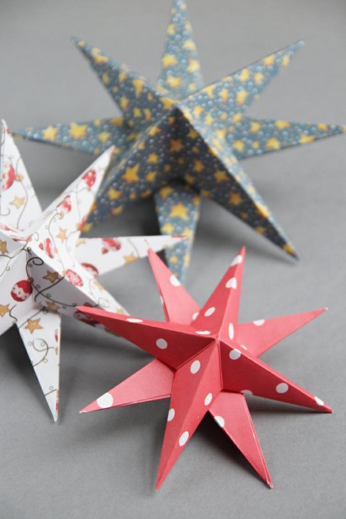 Weihnachtssterne basteln, drei Sterne aus buntem Papier, ein roter, ein weißer und ein blauer Stern