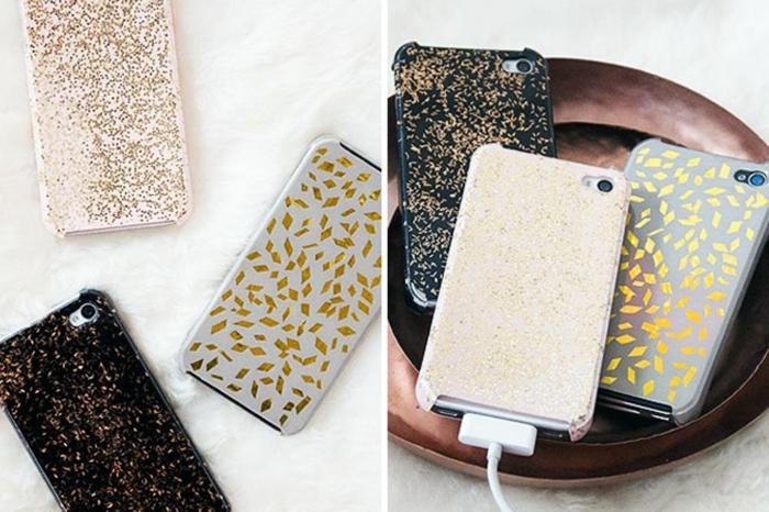 goldfarbene Dekorationen, schöne Handyhüllen in drei Farben, Rosa, Grau und Schwarz, in einer Schale