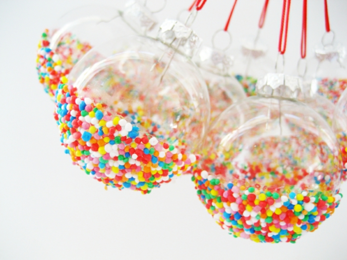 eine Menge bunte Kugeln mit Süßigkeiten bemalt, Weihnachtskugeln bemalen und mit roten Schnuren hängen
