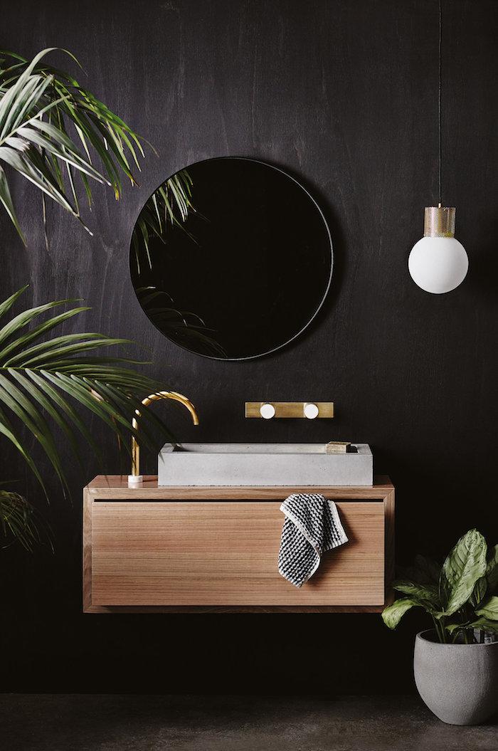 schwarze wand im badezimmer mit einem schwarzen spiegel und einer weißen vase mit grünen pflanzen, ein braunes waschbecken aus holz, weiße badezimmer lampe