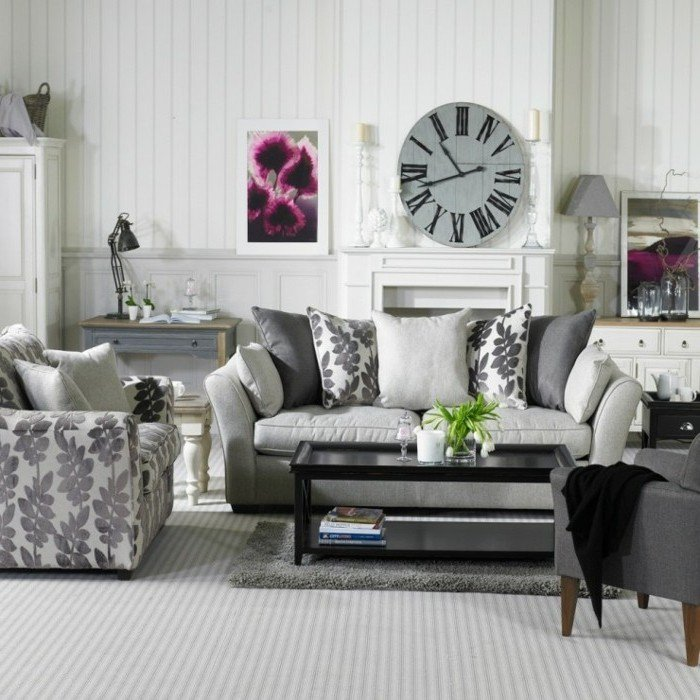 Wohnzimmer in Grau und Weiß, eine Wanduhr, ein graues Sofa und grauer Teppich, weiße Wandfarbe