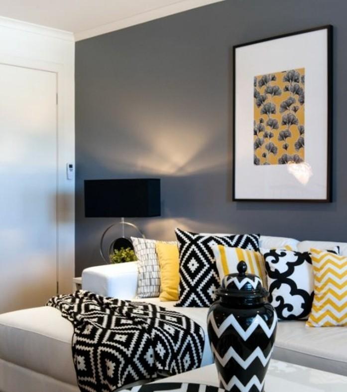 graue Wandfarbe, Wohnzimmer in Grau Weiß, gelbe Kissen und schwarz weiße Kissen mit verschiedenen Motiven