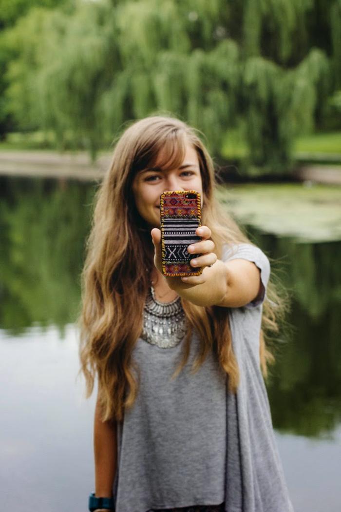 eine bildschöne Handyhülle designen, ein Mädchen mit blondem Haar trägt die selbstgemachte Handyhülle