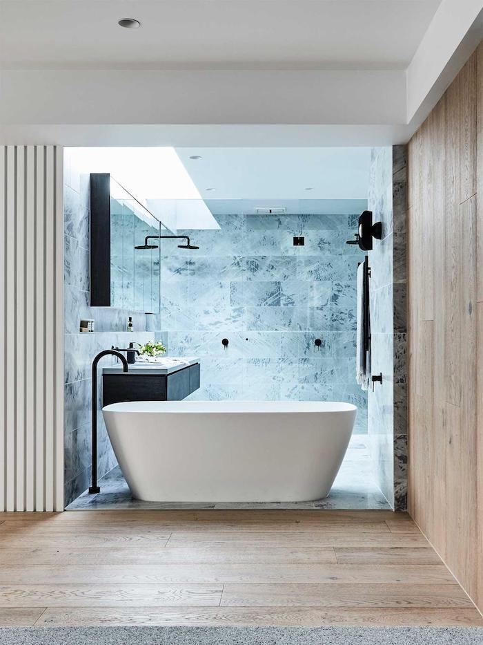 weiße freistehende badewanne im badezimmer mit einem braunen boden aus holz, badezimmer mit blauen wänden mit fliesen