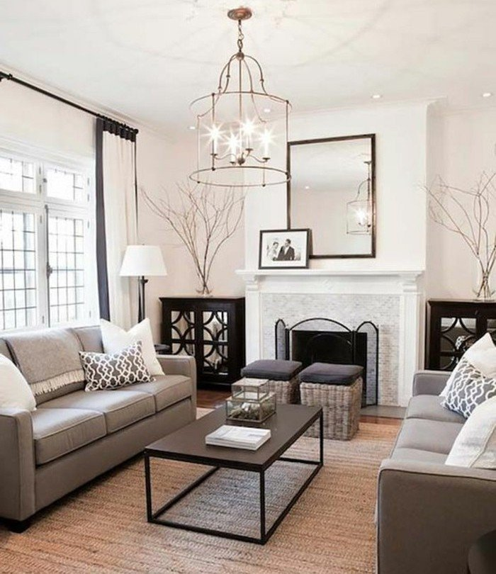 Wohnzimmer Grau Weiß, ein großer Spiegel, zwei Hocker, ein schwarzer Tisch, brauner Teppich