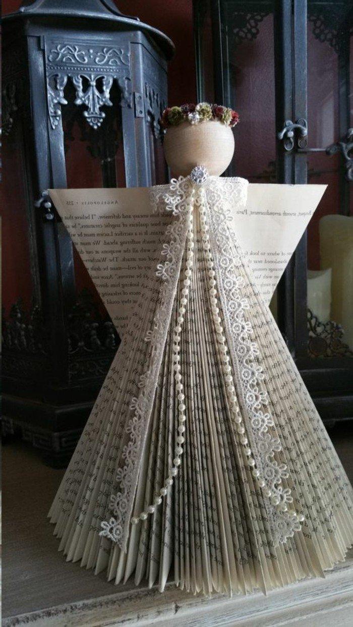 ein weißer Engel mit Spitzen und Perlen geschmückt, ein Kopf aus Holz, Buchseiten falten