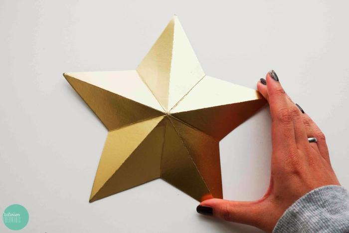 Weihnachtssterne basteln, ein goldener Stern mit fünf Strahlen, aus goldenem Papier gefaltet