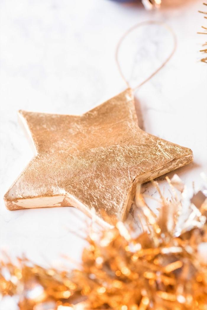 Sterne basteln, Stern mit Blattgold bedeckt und eine goldfarbene Girlande, Weihnachtsbaum Deko