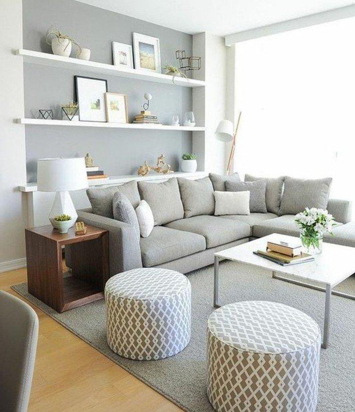graue Ecksofa, weiße Regale mit Bildern, zwei weiße Hocker, eine weiße Lampe, Wohnzimmer Grau Weiß
