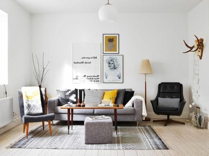 ein graues Sofa, gemusterter Teppich, zwei Sessel, drei Bilder, viele Bilder, Wohnzimmer in Grau Weiß