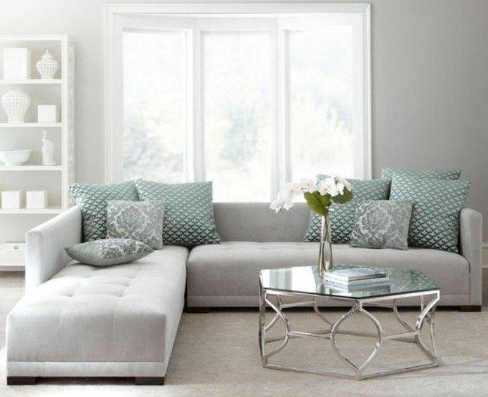 ein graues Ecksofa, grüne Kissen, ein Tisch aus Glas, ein Fenste mit weißem Rahmen, welche Farbe passt zu Grau