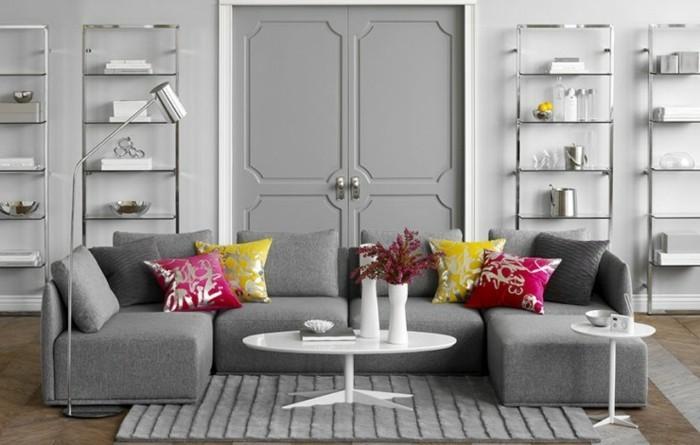 ein graues Sofa mit Kissen in rosa und gelber Farbe, ein kleiner runder weißer Tisch, Welche Farbe passt zu Grau