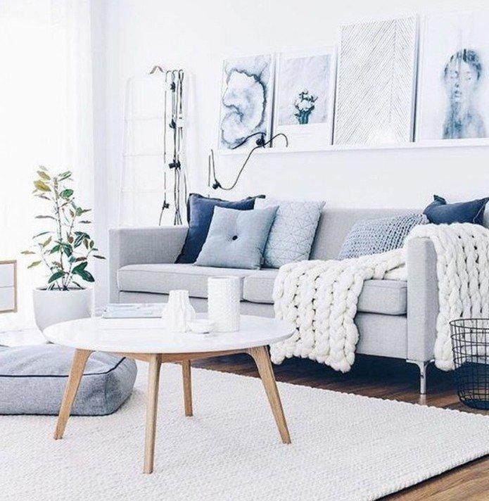 ein graues Sofa, ein weißer runder Tisch, graue Kissen, eine weiße Leistne mit modernen Bildern