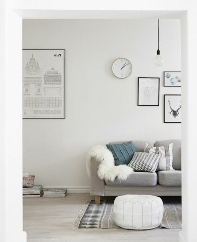 Wohnzimmer streichen Weiß Grau, ein graues Sofa, weiße Wandfarbe, weiße Wandihr, weißer Hocker und grauer Teppich