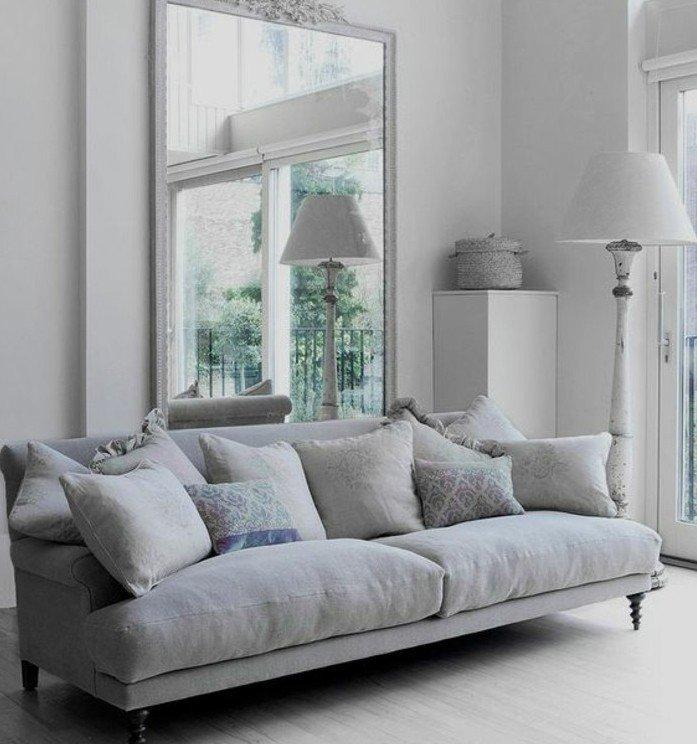 ein großer Spiegel und ein graues Sofa, ein weißer Teppich, Wohnzimmer streichen Grau Weiß