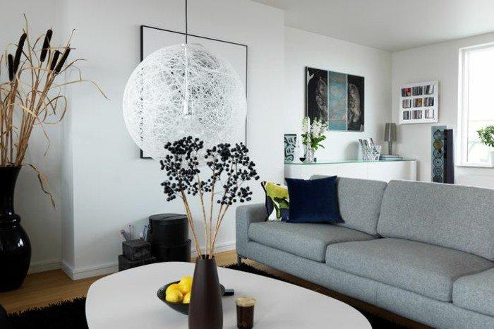 ein graues Sofa, ein weißer Tisch, eine runde Lampe, eine schwarze Vase, Wohnzimmer in Grau Weiß