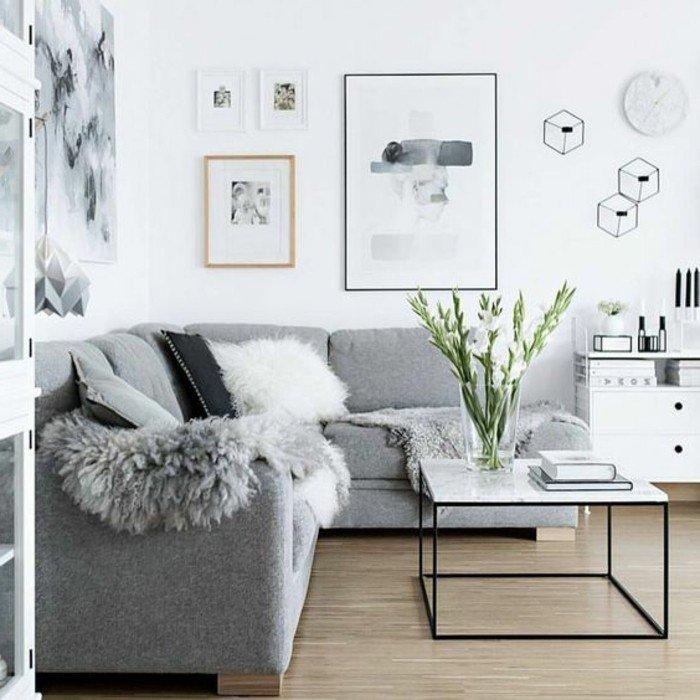 Wohnzimmer streichen Grau Weiß, ein graues Sofa, ein weißer Tisch, Laminat Boden, moderne Bilder an den Wänden