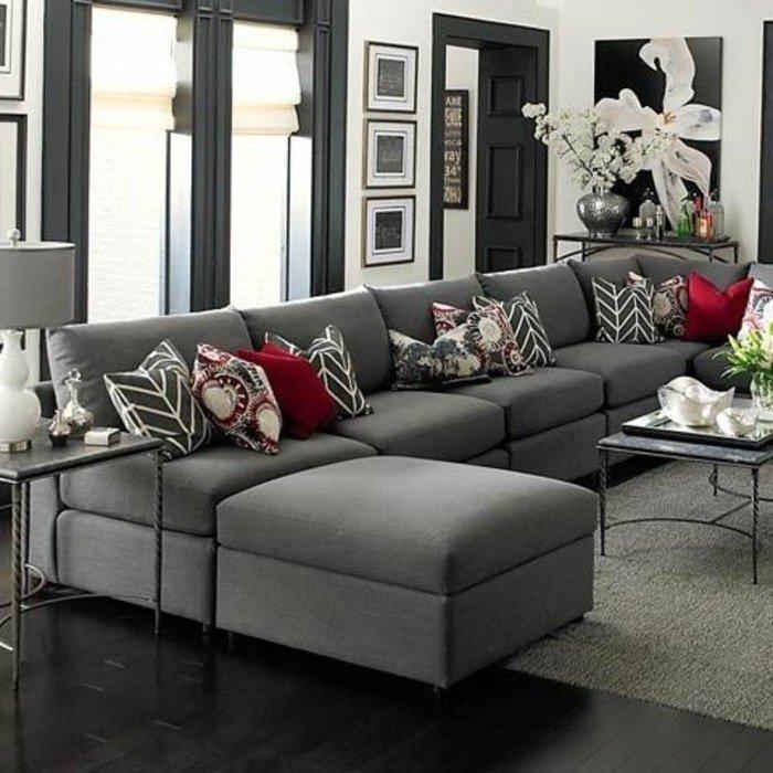 Wohnzimmer streichen Grau Weiß, eine Eckcouch, rote Kissen, grauer Teppich, eine weiße Blume auf Bild