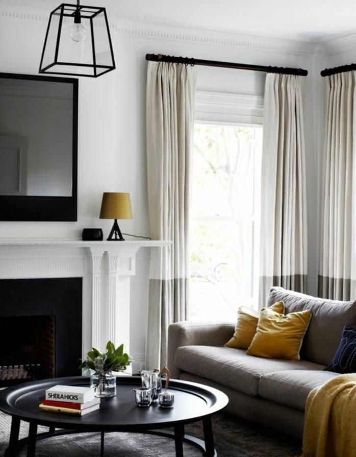 Wohnzimmer streichen Grau Weiß, weiße Vorhänge, ein Spiegel über dem Kamin, ein runder Tisch