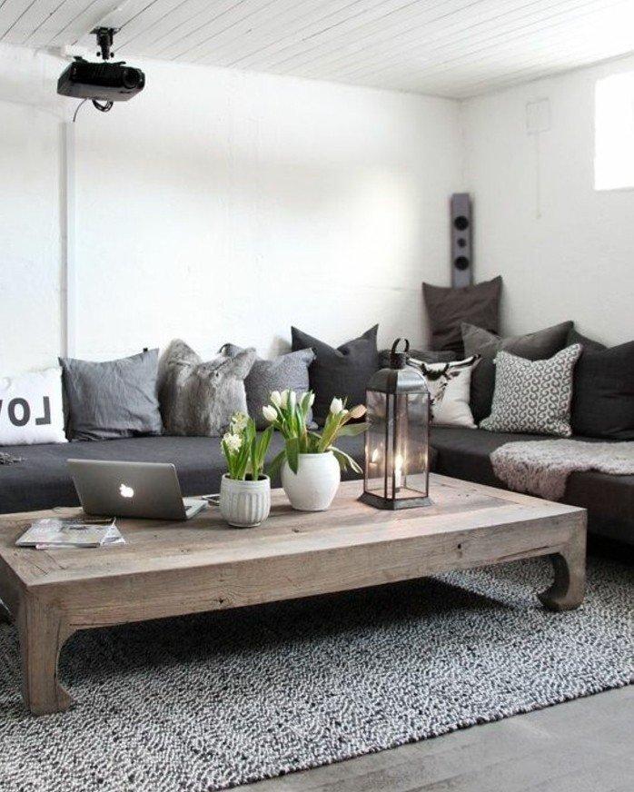 ein Tisch aus Holz, ein graues Sofa, Vasen in weißer Farbe, Wohnzimmer streichen Grau Weiß
