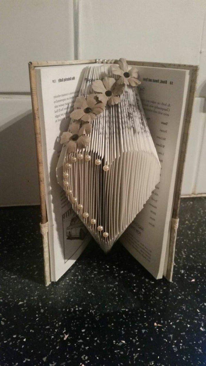 ein Herzchen mit Perlen geschmückt, kleine Blüten verschönern das Bild, Bücher falten