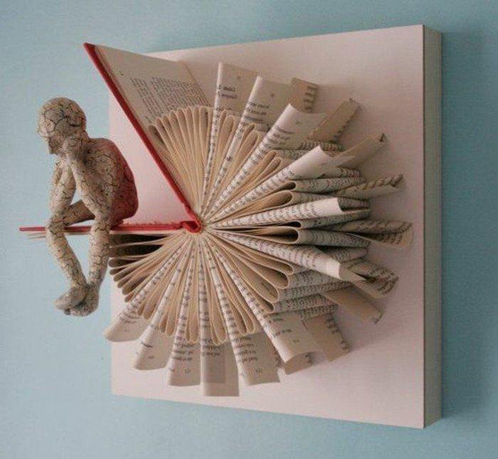 eine Skulptur von einem Menschlein, das auf dem Umschlag sitzt, Origami Buch wie eine Blume