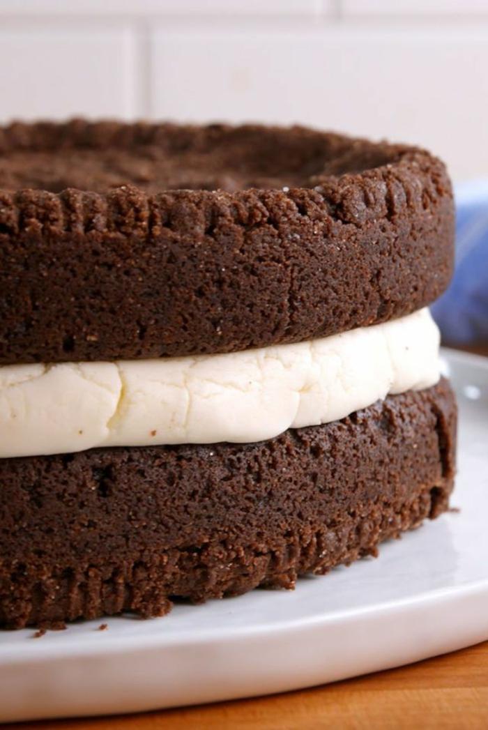 zwei Schokoladenböden, weiße Creme in der Mitte, ein großer Oreo Keks, Oreo Torte mit Milchcreme